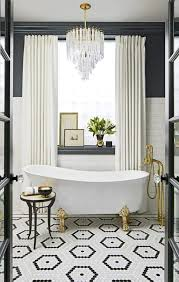a free standing bathtub on brass clawfeet and a crystal chandelier over it