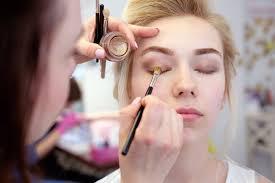 makeup artist doing a blonde woman s eye shadow application