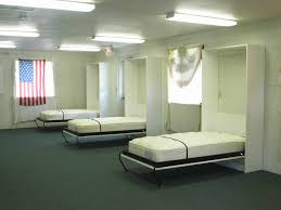 simple white twin sized wall beds installed in a local firehouse script type text javascript