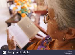 old lady reading book on armchair in hoe