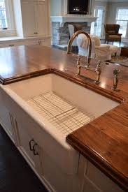 distressed walnut countertop with a sink designed by studio 76 kitchens baths