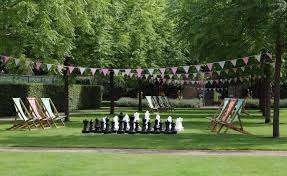 the walled garden green with wooden sun loungers and giant chess set