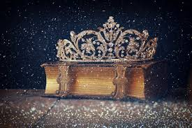 low key image of decorative crown on old book vine filtered stock photo