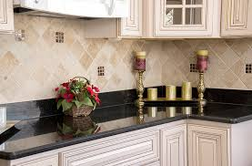 black galaxy granite countertops matched with an off white cabinet and classic travertine tile backsplash