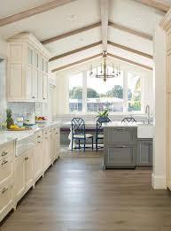 exquisite cream and gray kitchen is accented with a gray wash oak island fitted with satin nickel cup pulls and a white quartz countertop finished with a