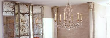 our danieli chandelier reflects light in the antiqued mirrors of a set of sevigne screen panels