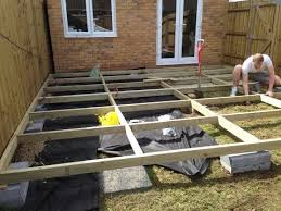 installing a basic raised frame decking with reclaimed scaffold boards over a sloped lawn