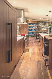 wide plank black walnut hardwood floor by oak and broad modern kitchen area with black