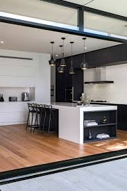 modern white and black kitchen. A Modern Black And White Space With Sleek Cabinets Eye-catchy Pendant  Lamps Over Kitchen