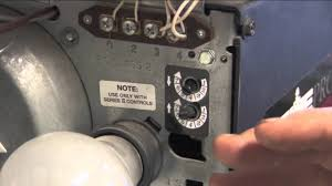 a close up of a garage door opener focuses on two knobs marked with a