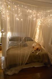 rustic queen bedroom design with hanging white string lights and canopy bed curtains from ceiling over bed ideas