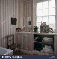 grey and white striped wallpaper in townhouse bathroom with towels d on open shelving in fitted unit
