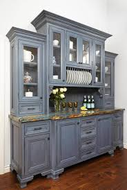 classic kitchen flanking buffets with hutch featuring raised panel wooden door cabinets with nickel pulls and upper plate racks plus marbled counter