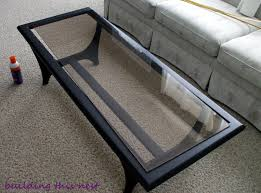 furniture black wooden base with rectangle glass top table having black frame placed on the