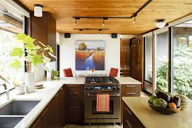 luxurious mid century modern kitchen with wooden cabinet plus stove also track ceiling lamps