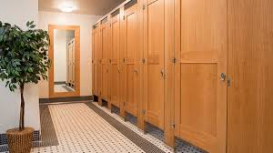 black and white tiled floor in theater bathroom with six oversize wood veneer partitions featuring captured