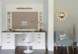 white desk with wood top under bulletin board and picture light