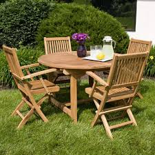 backyard outdoor dining area with expandable round oak dining table and 4 wood folding chairs beside garden ideas