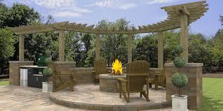 paver patio space with outdoor kitchen sitting wall round block fire pit and wood pergola
