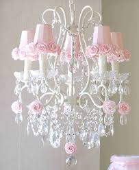 white chandelier with five white candle lamps plus pink cup completed with pink roses ornaments around also placed on the glass tray feat crystal hanging