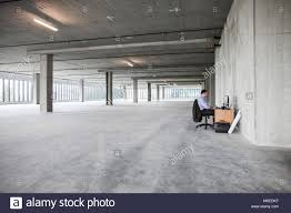 large office space. Businessman Sitting At A Small Desk In Large Empty Raw Office Space. Space O