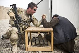 photo essay years of war warrior scout a us army ier and a member of the afghan uniform police arm wrestle prior to a joint patrol near command outpost ajk short for azim jan kariz