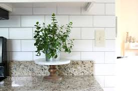 Make a White Subway Tile Temporary Backsplash with removable wallpaper.  Follow this tutorial for a