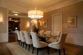 contemporary dining room design with round oversized chandeliers above glass table and white leather tufted chair
