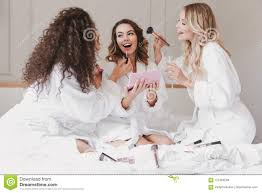 young happy bride and bridesmaids 20s wearing housecoat drinking chagne and applying makeup during bridal shower while resting in luxury bedroom at hotel