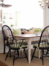 this country dining setting features a farmhouse table with black windsor chairs and bench to give