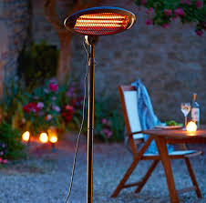 a tall patio heater standing next to an outdoor wooden table and chair set