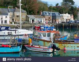 man painting his fishing boat in the harbour padstow cornwall england uk