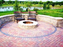 round fire pit on patio with cement brick pavers in a herringbone pattern