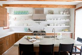 this kitchen has a mix of both open and closed shelving but keeps the pretty things on display and makes sure that the sparkling water supply is always