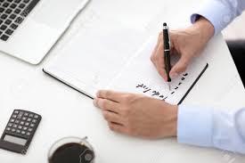 Standard Office Equipment List Businessman Writing To Do List At Table In Office Lizenzfreie Fotos