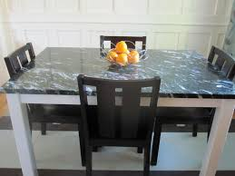 astounsding white wooden dining table with black marble top combine with black dining chairs also wire bowl fruit stand