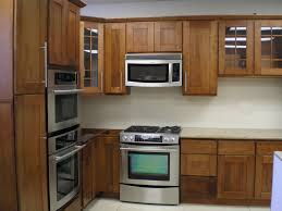 spacesaver small kitchen desgin with wall mounted microwave shelf above stove under oak kitchen cabinet with glass door and white backsplash ideas