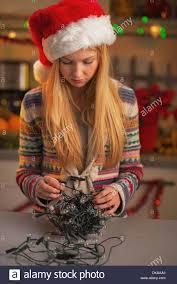 Untangle Christmas Tree Lights Frustrated Teenage Girl In Santa Hat Untangling Christmas