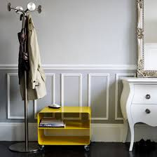 pale grey hallway with panelling small table chest of drawers and coat stand