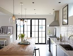 three pendant lights from west elm are suspended over a knotty surfaced farm table in the kitchen one of the few holdovers from the homeowners previous