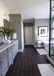 This high contrast bathroom features both large format worn black floor  tiling and a raised black