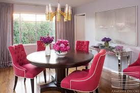 view full size an acrylic and br chandelier illuminates a round dining table lined with hot pink tufted dining chairs