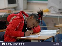 african american girl in th grade english class raises hand while african american boy in 9th grade english class works on writing skills while developing