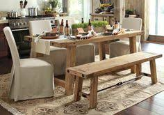 rustic kitchen with reclaimed table and slipcovered chairs
