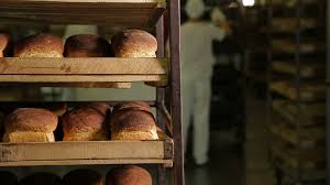 Working In A Bakery Trays With Freshly Baked Bread At The Bakery On
