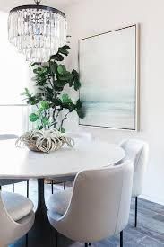 elegant dining room featuring a restoration hardware 1920s odeon clear glass fringe 3 tier chandelier over a round marble top tulip dining table with white
