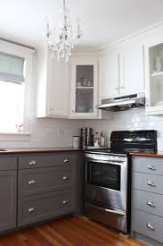 two toned kitchen wall cabinet with dark wooden countertop with white tile backsplash and frosted