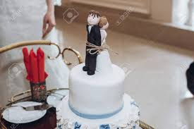 Funny Wedding Cake Topper Figurines Of Bride And Groom Tied Stock