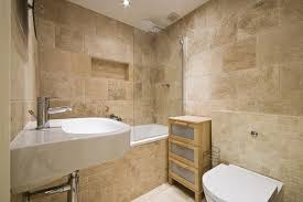 A Bathroom With Travertine Tiles And Mosaics On The Shower Walls Floors