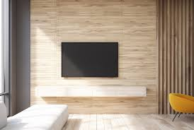 a minimalist living room with a wall mounted tv above a floating shelf